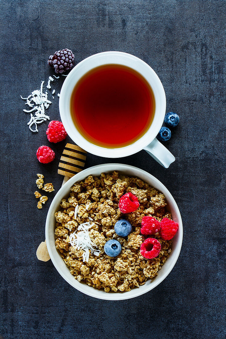 Granola muesli with berries and a cup of tea (top view)
