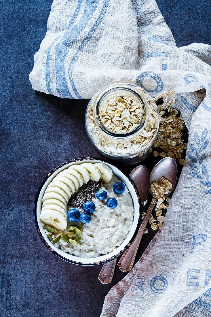 Vintage ceramic bowl of healthy oatmeal porridge, bananas, blueberries, pumpkin and chia seeds on dark grunge background