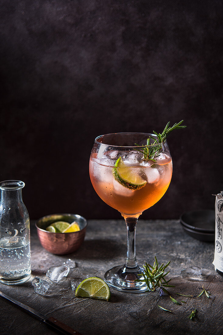 Pink gin and tonic cocktail with angostura bitters, lime and rosemary, tonic water beeing poured