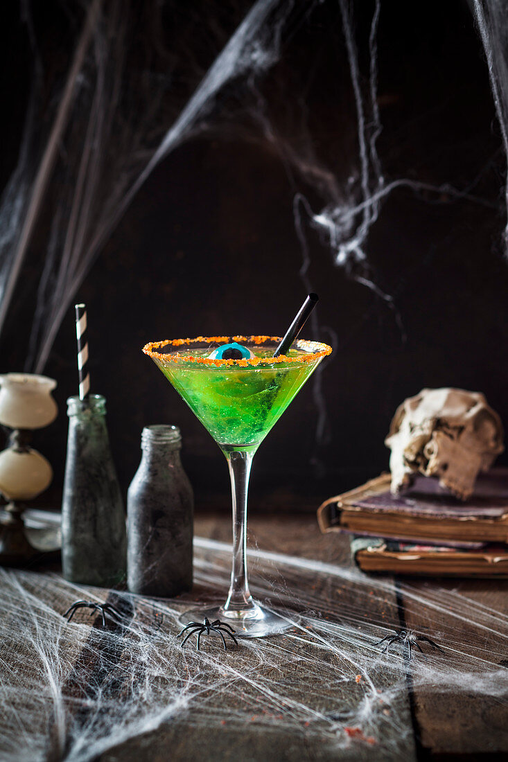 A children's cocktail made from green jelly and apple juice decorated with an eye sweet for Halloween