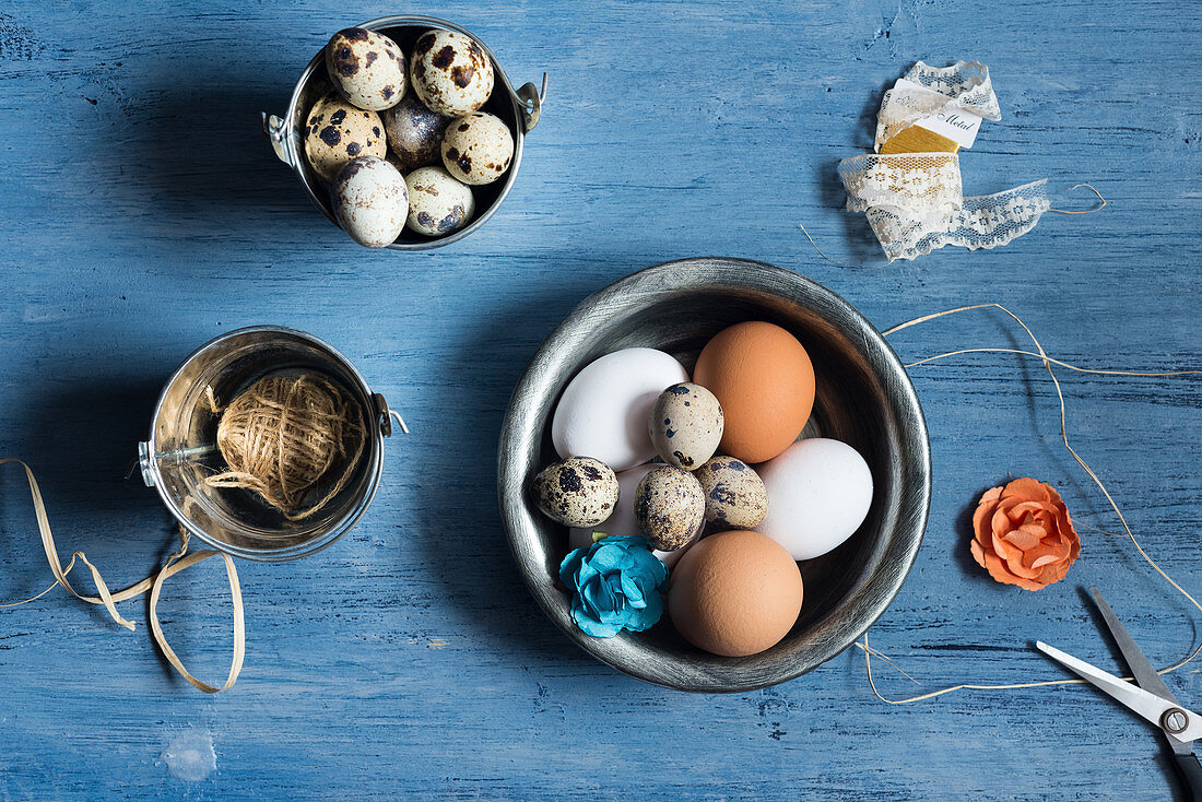 Assortment of eggs, decor elements on a rustic blue wooden background