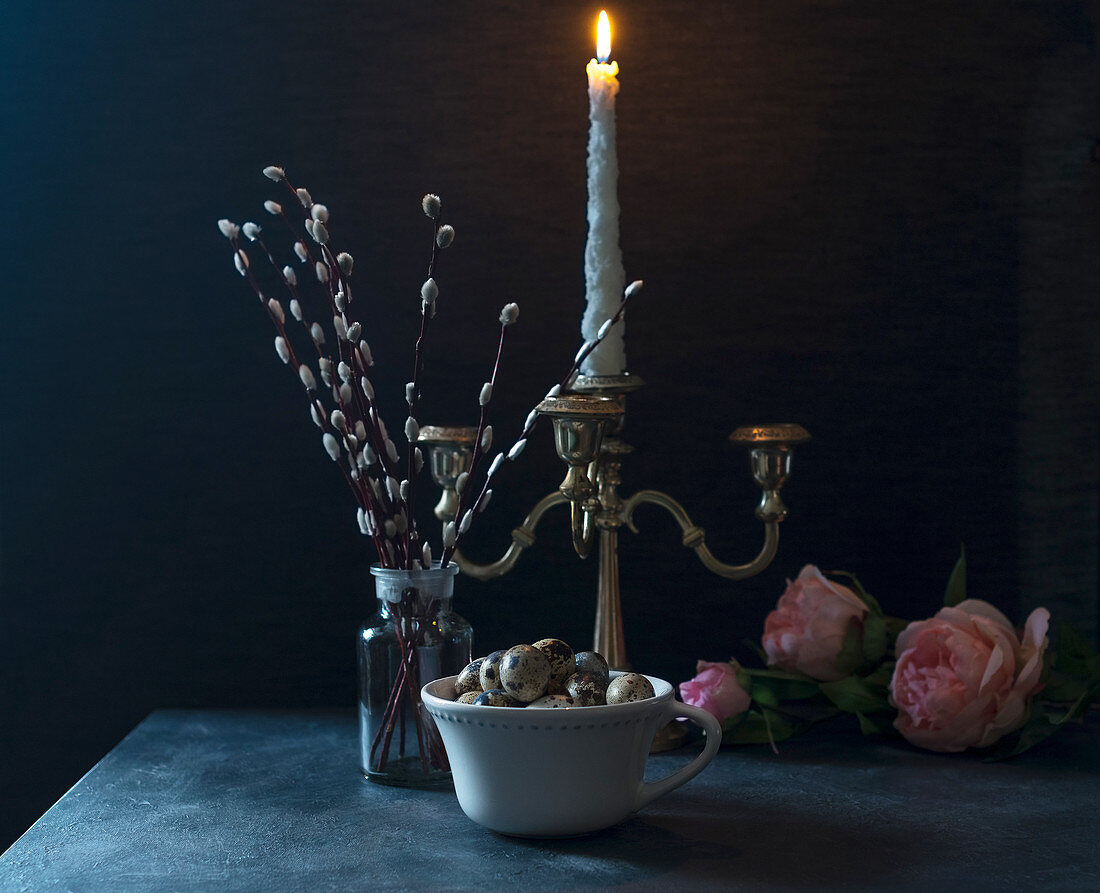 Still life of a bowl of quail eggs, a burning candle, willow branches and flowers, retro styled