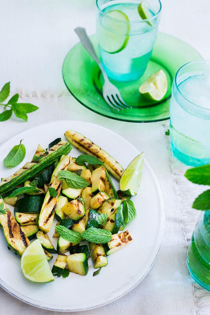 A plate with grilled zucchini, mint leaves and lime wedges