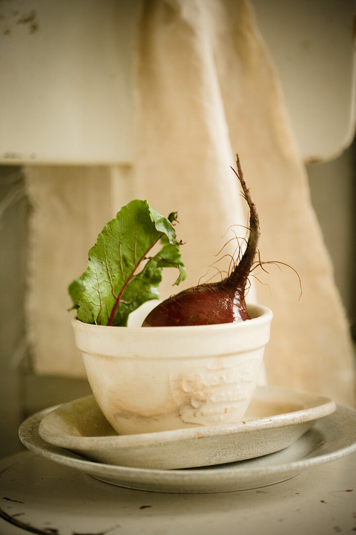 Beetroot with a leaf sticking out of a ceramic mug