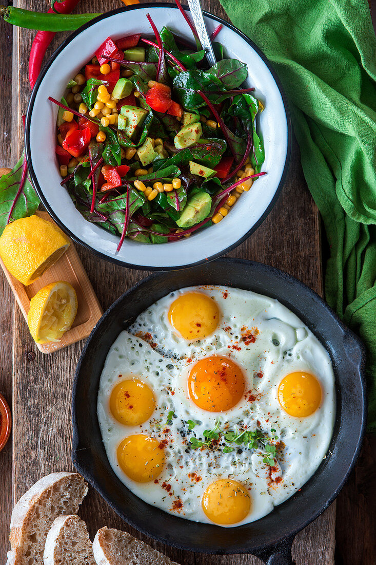 Fried eggs and salad with corn, avocado and pepper