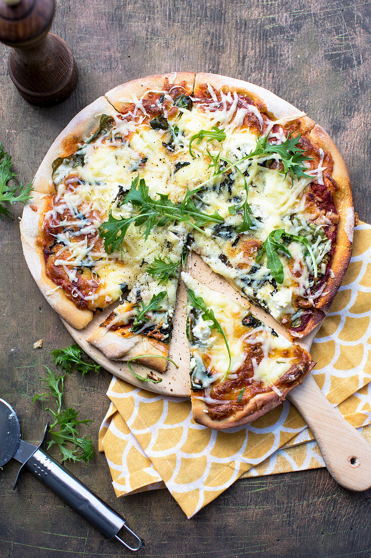A three cheese pizza with rocket