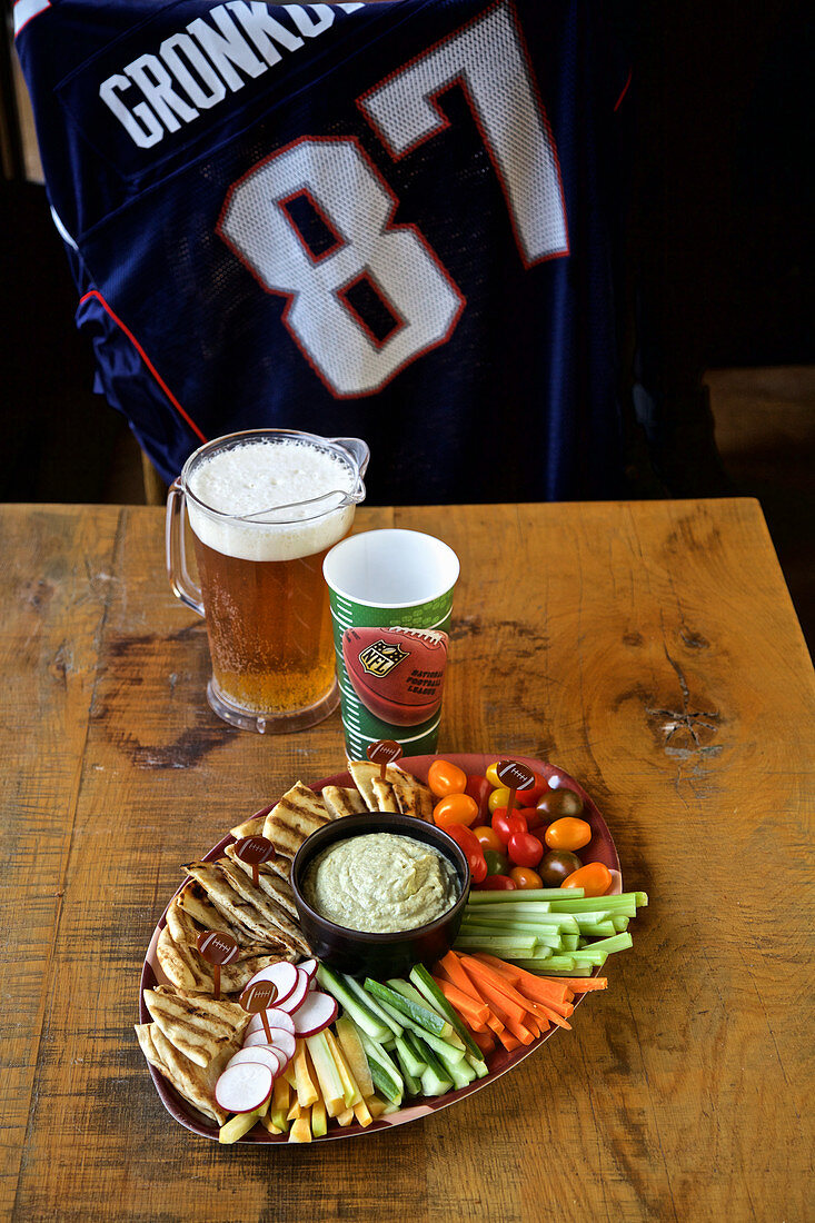 Vegetables with dip and beer, NFL shirt in a background (USA)