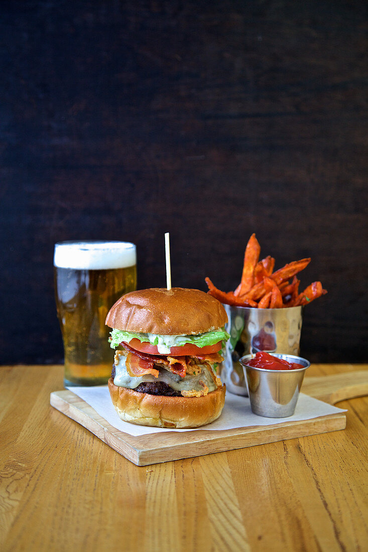 Cheese burger with lettuce tomato, onion, sweet potato fries, ketchup and beer