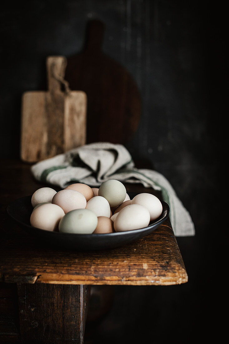 A bowl of naturally dyed eggs on a wooden table