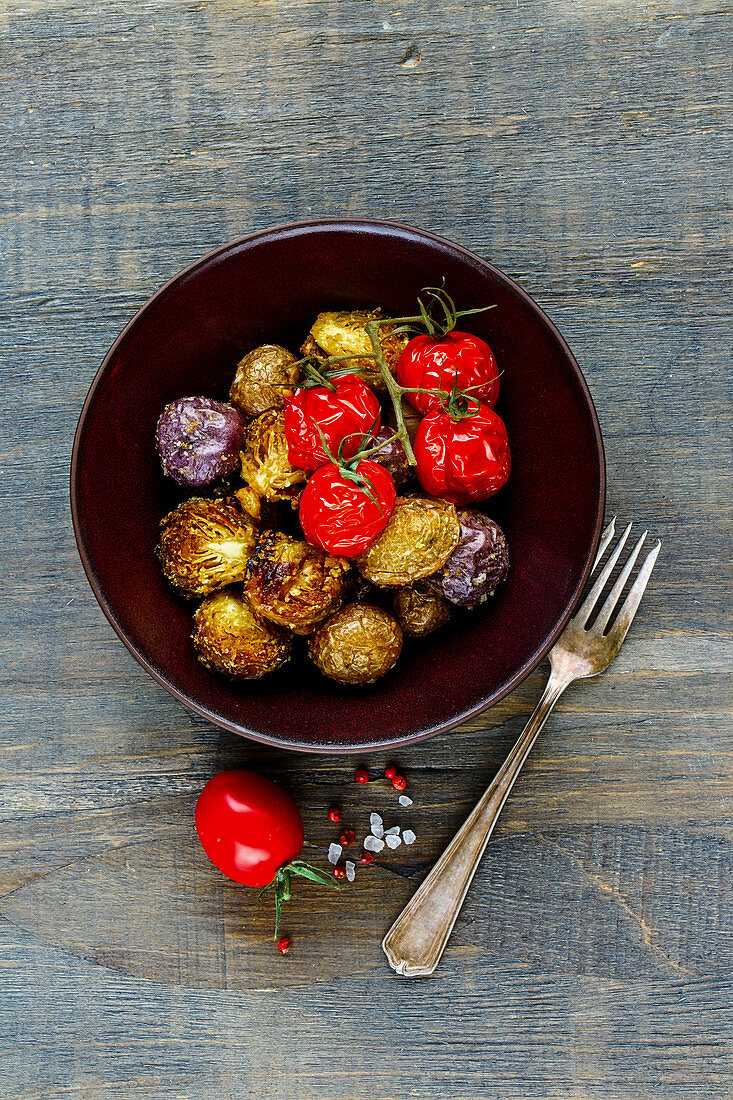 Oven-baked potatoes, Brussels sprouts and cherry tomatoes in a bowl