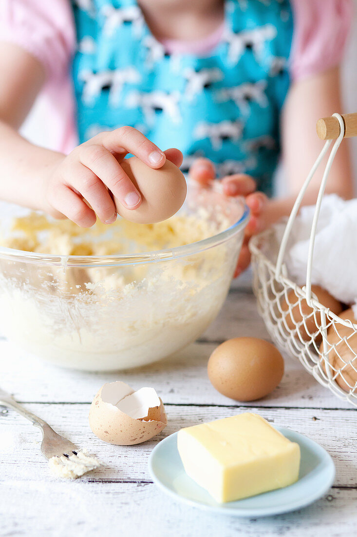 Child Cracking Eggs into a Mixing Bowl