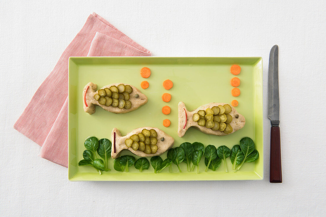 Mini fish cakes with gherkins, carrots and lamb's lettuce