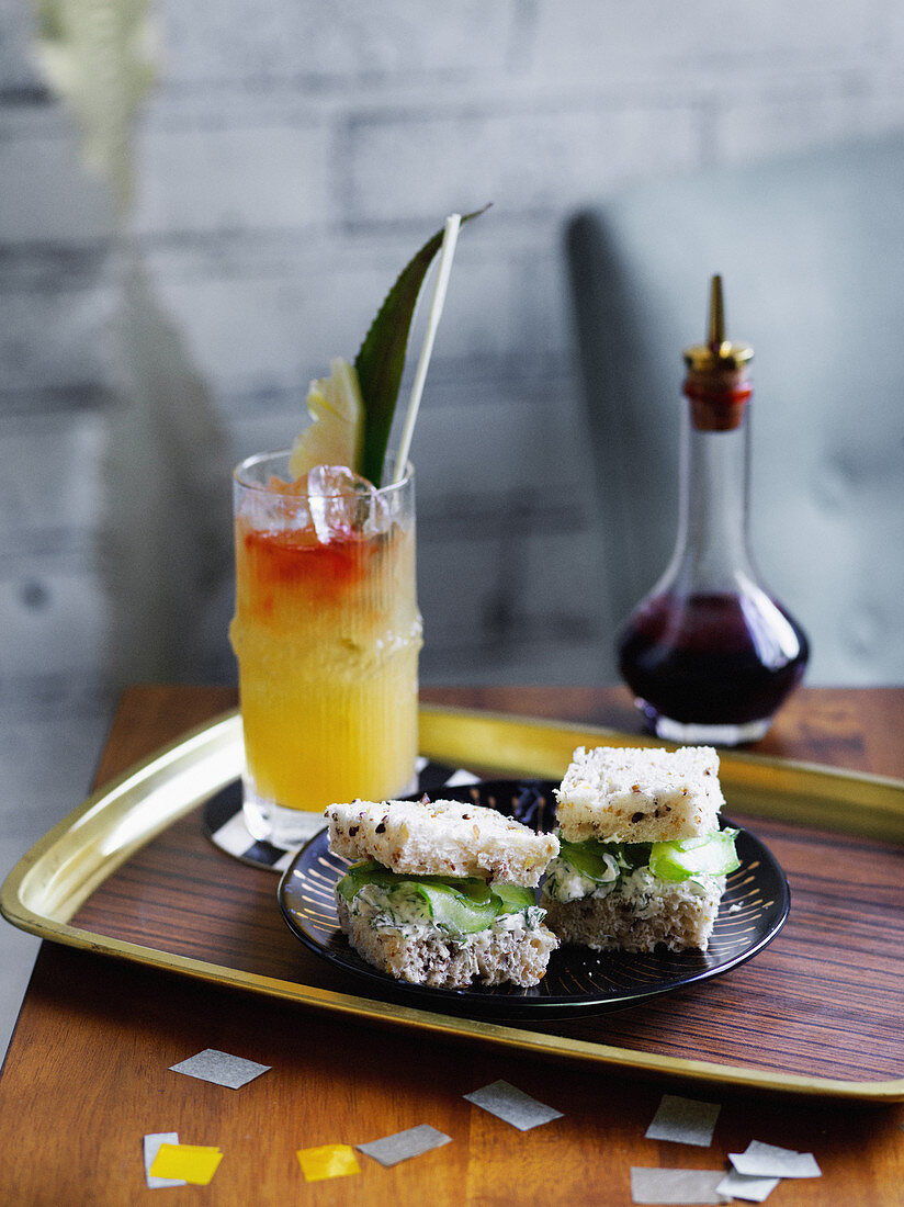 Rum Punch with cream cheese, herb and cucumber tea sandwiches (1960s)