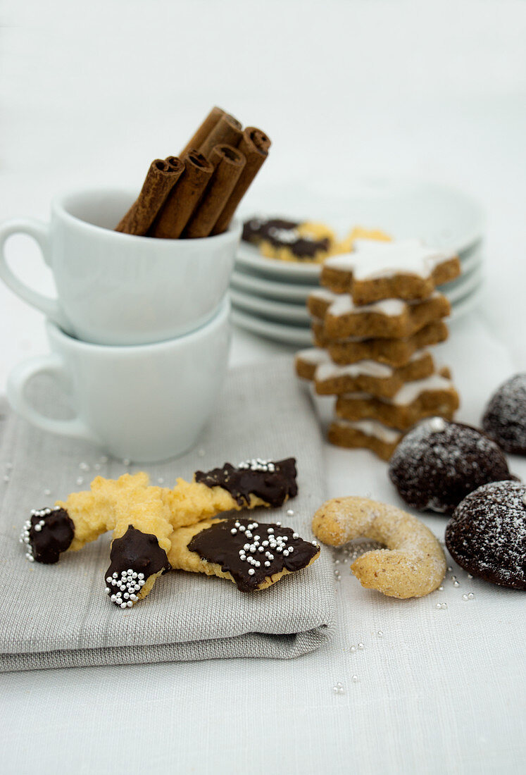Various Christmas biscuits and espresso cups with cinnamon sticks