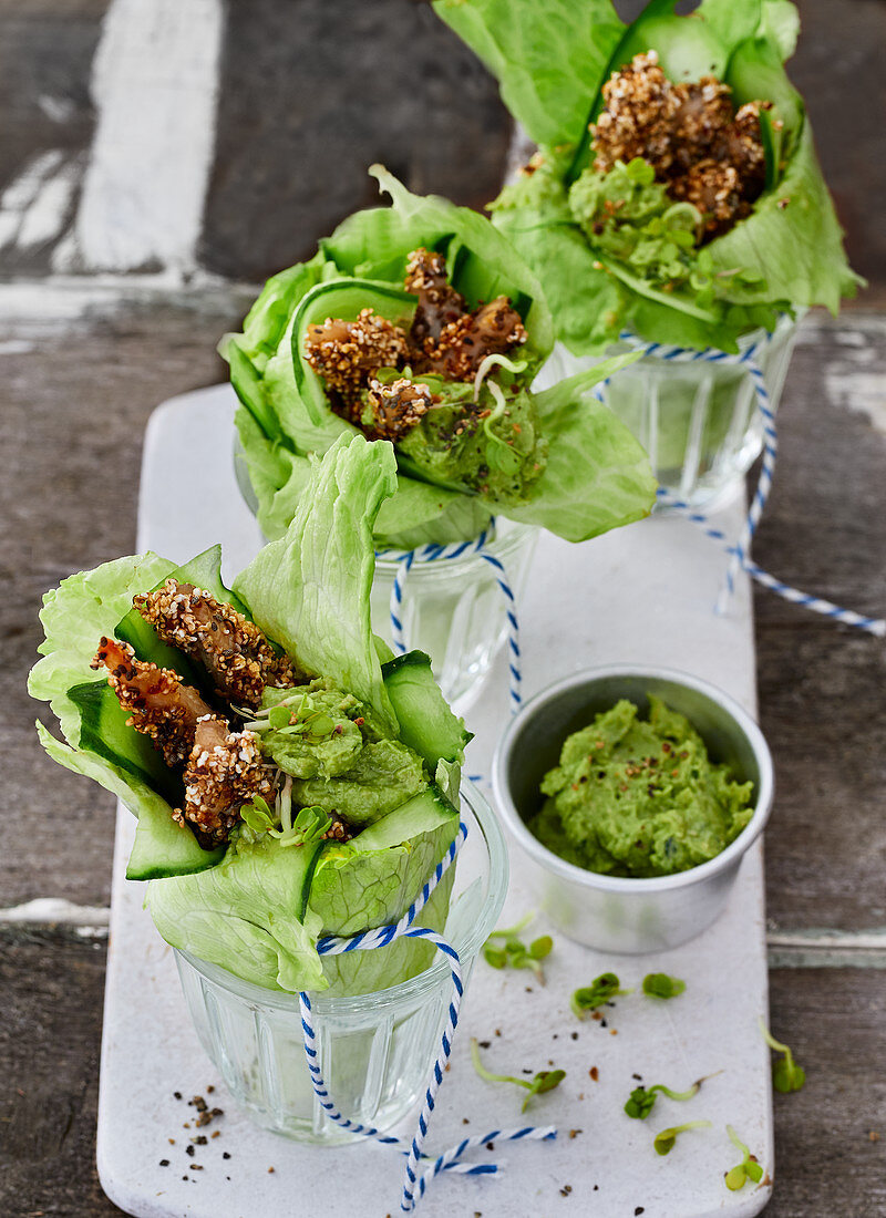 Chicken breast with an avocado dip, radish shoots and chia seeds in iceberg lettuce