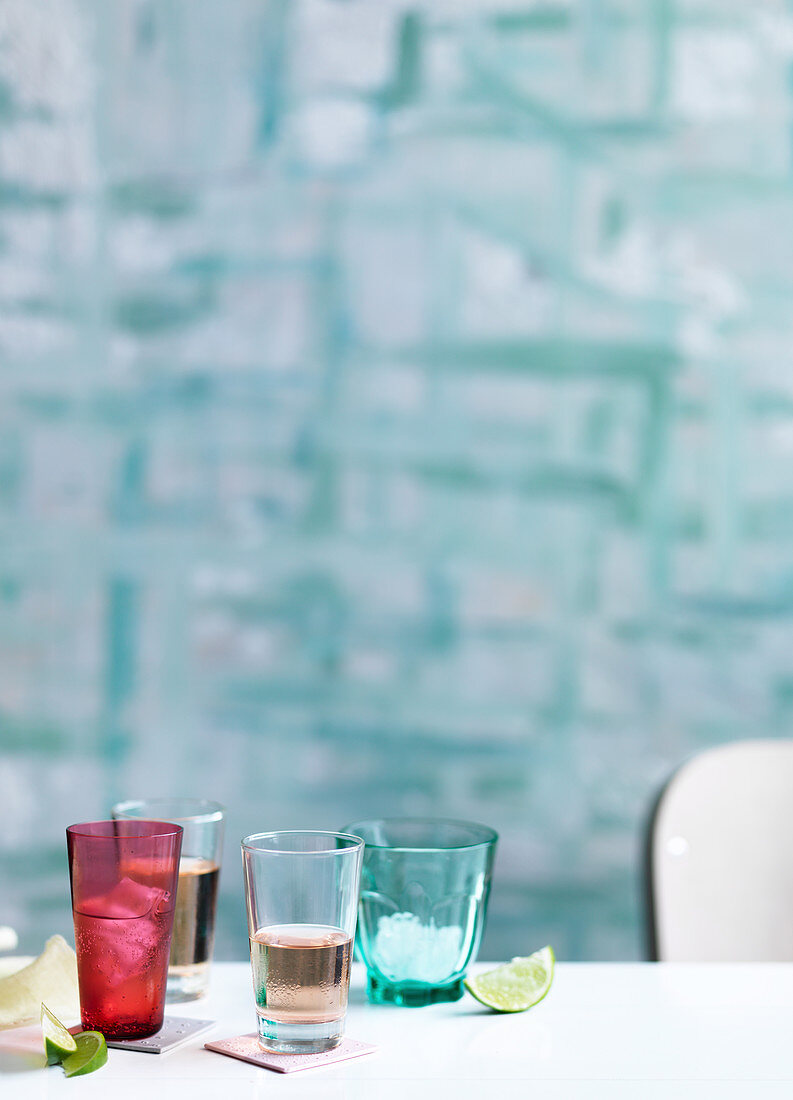 Coloured glasses, pink, lime wedges, blue background