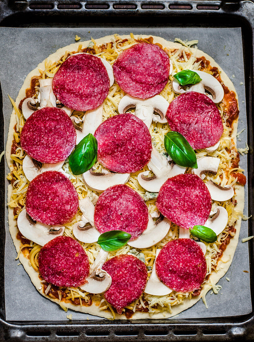 An unbaked salami and mushroom pizza