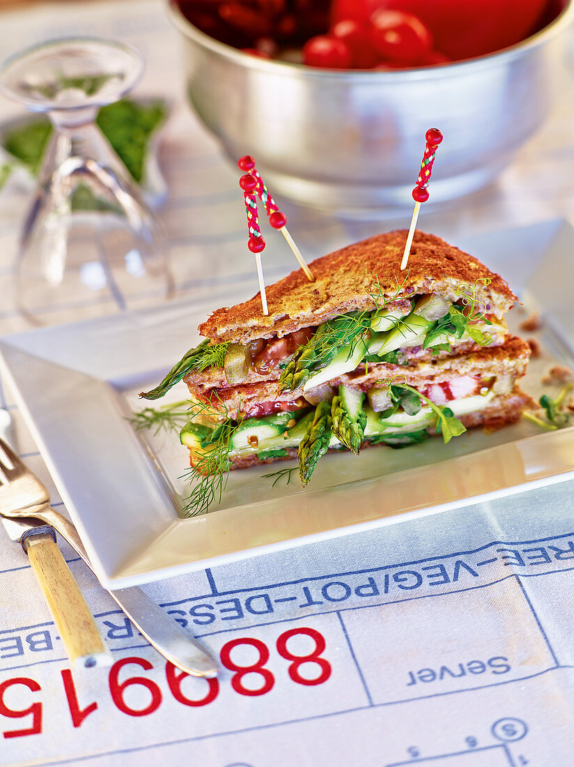 A double-decker sandwich with green asparagus, alpine cheese and herbs