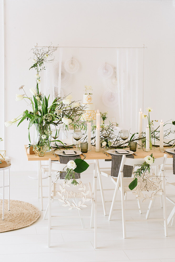Table set for wedding with vase of tulips, dry twigs and pillar candles in front of wedding cake on sideboard