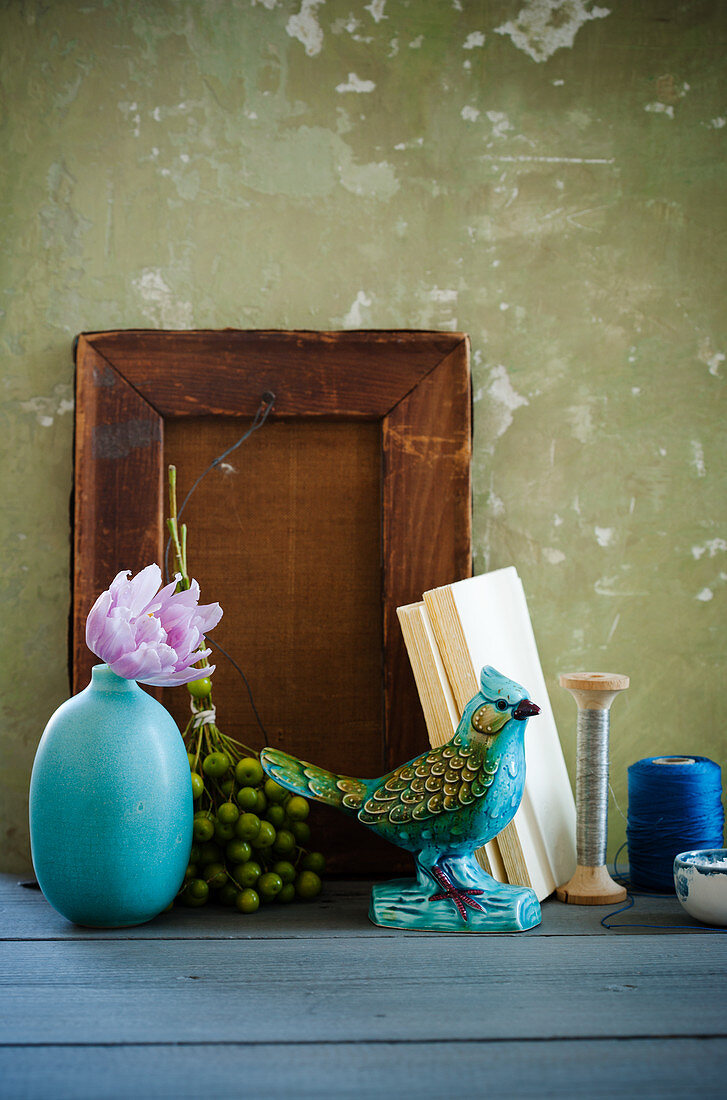 Still-life arrangement of china bird, vase, posy of berries and wooden board