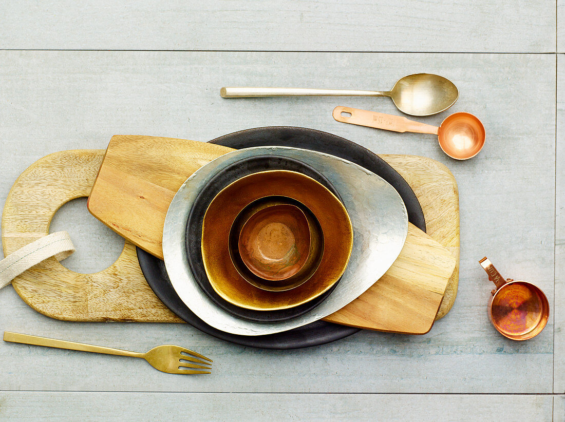 Various bowls and boards next to cutlery, a copper jug and a copper spoon