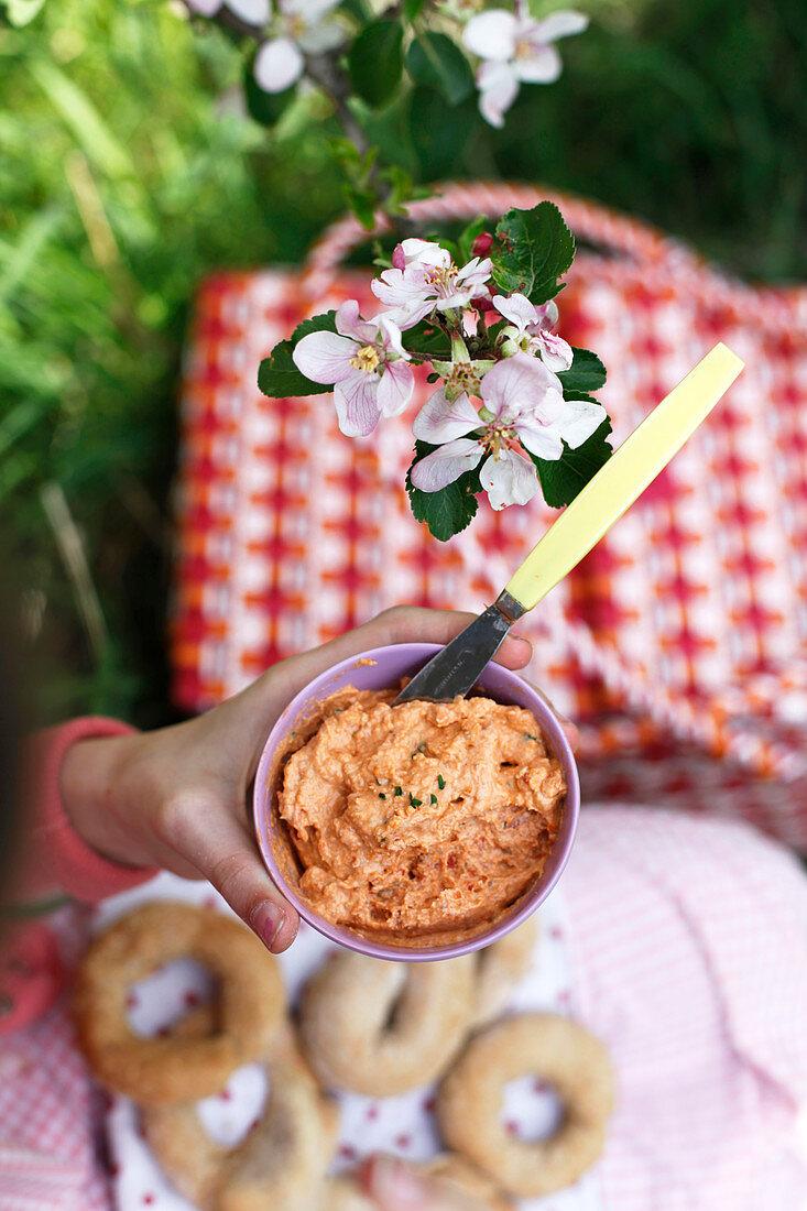 A girl having a picnic with tomato cream and sesame bread