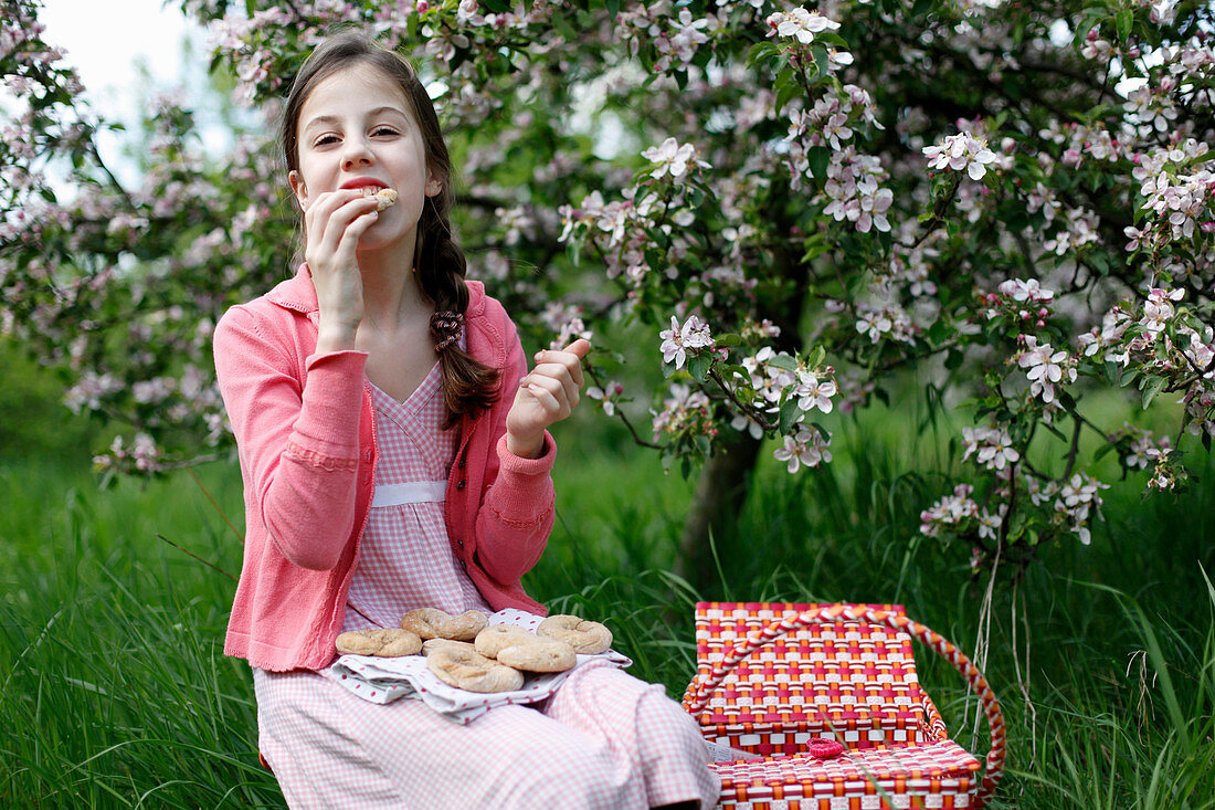 A girl having a picnic in a meadow amongst apple trees