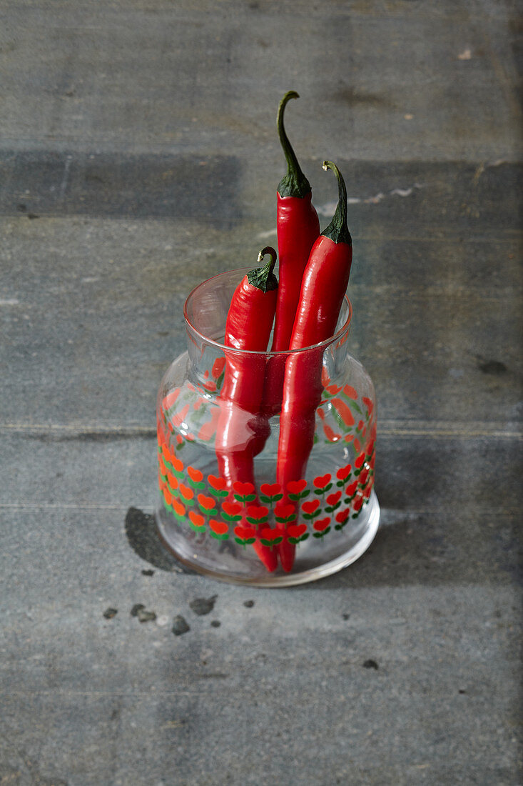 Three fresh red chilli peppers in a glass jar