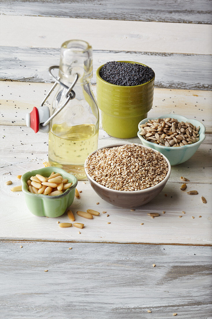 Pine nuts, sesame seeds, sunflower seeds, poppy seeds and a bottle of oil