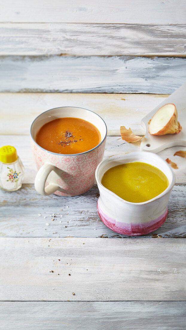 Two healthy cups of soup: tomato soup and pumpkin soup