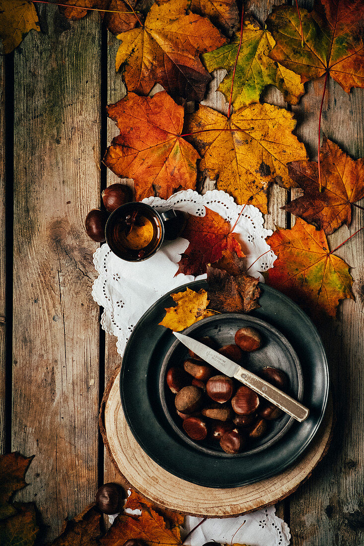 Autumnal still life with chestnuts, a cup of tea, and leaves (top view)
