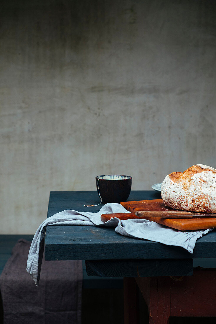 A still life with a loaf of bread and tea bowls on a table