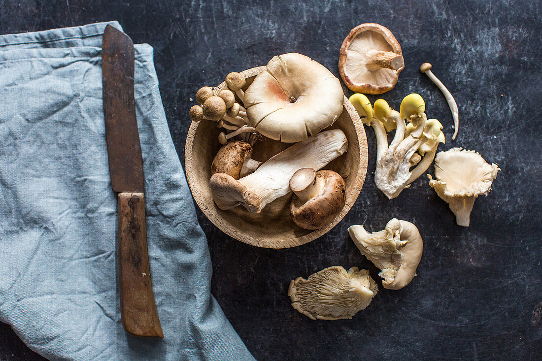 Various fresh mushrooms in a wooden bowl and next to it