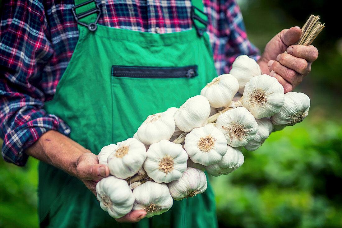 A man holding a garlic plait