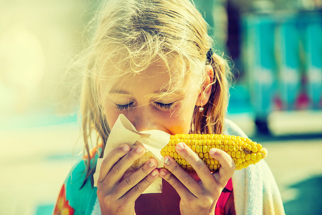 A girl eating a grilled corn cob