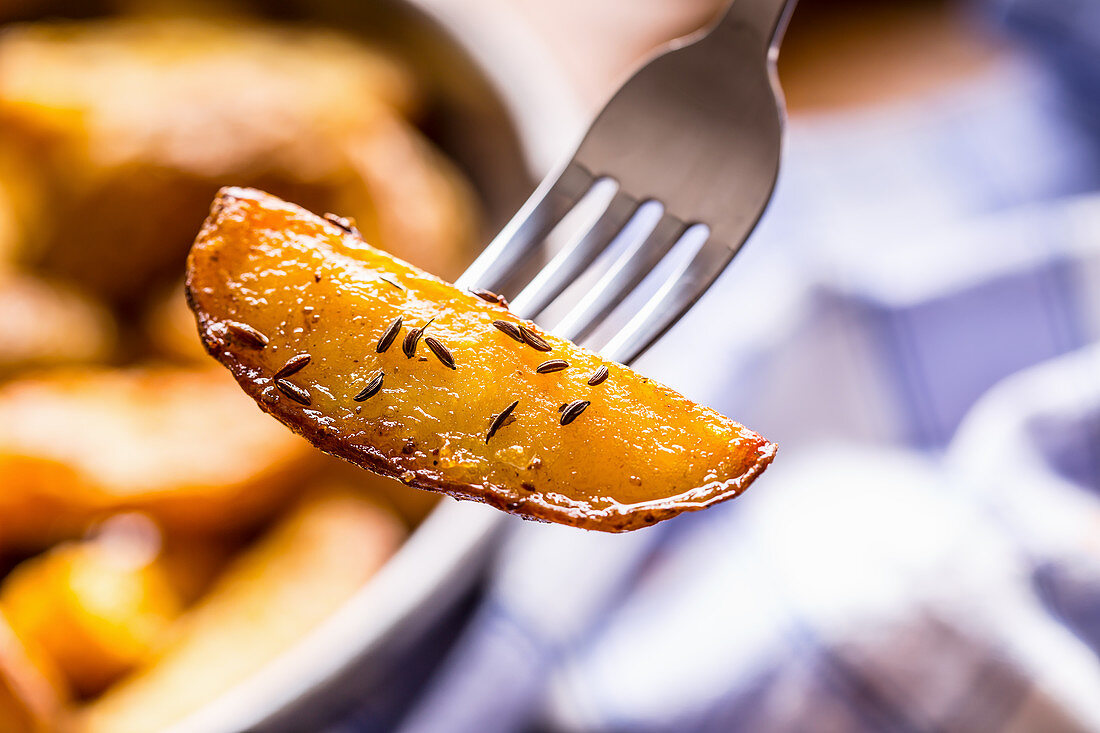 Roasted potato wedges with caraway seeds on a fork (close up)