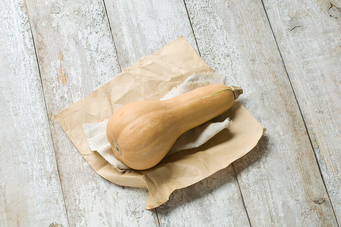 A butternut squash on a rustic wooden table