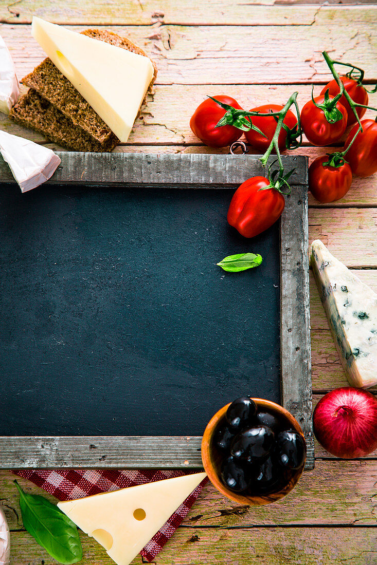Italian cuisine: a chalkboard surrounded by cheeses, tomatoes, onions and olives