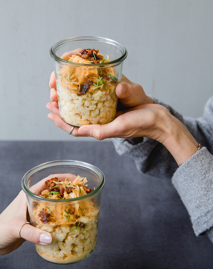 Spätzle (soft egg noodles from Swabia) with creamy sauerkraut and crispy bacon in a jar