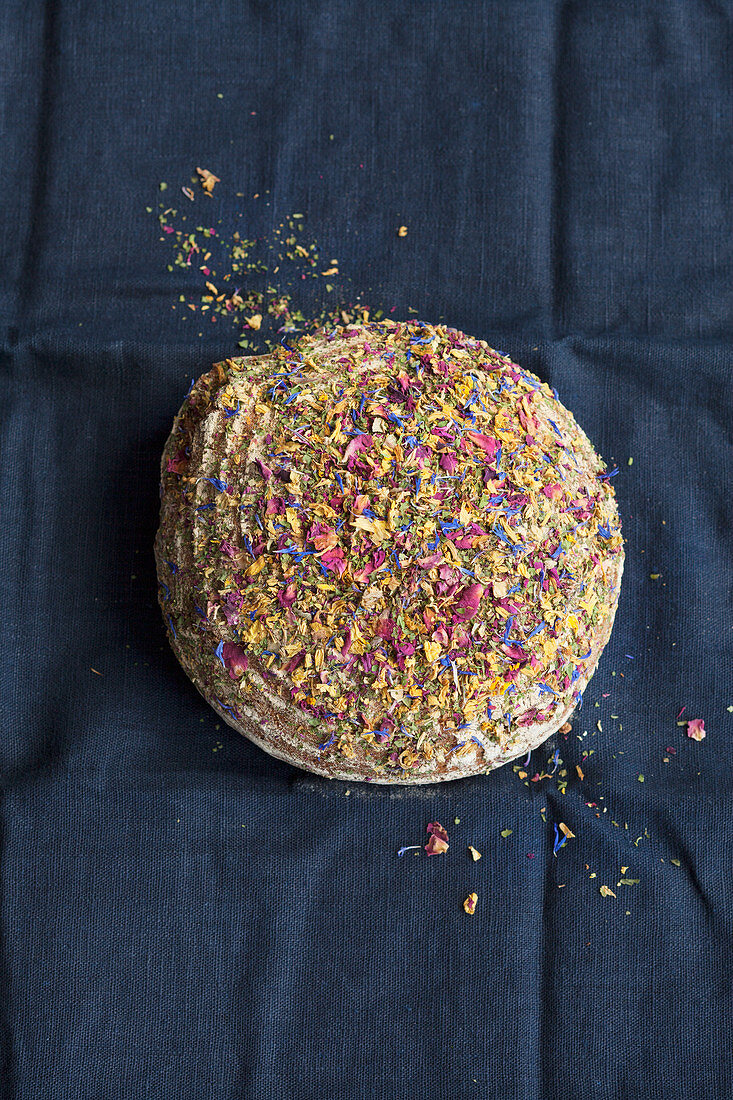 A loaf of wholemeal bread topped with edible flowers