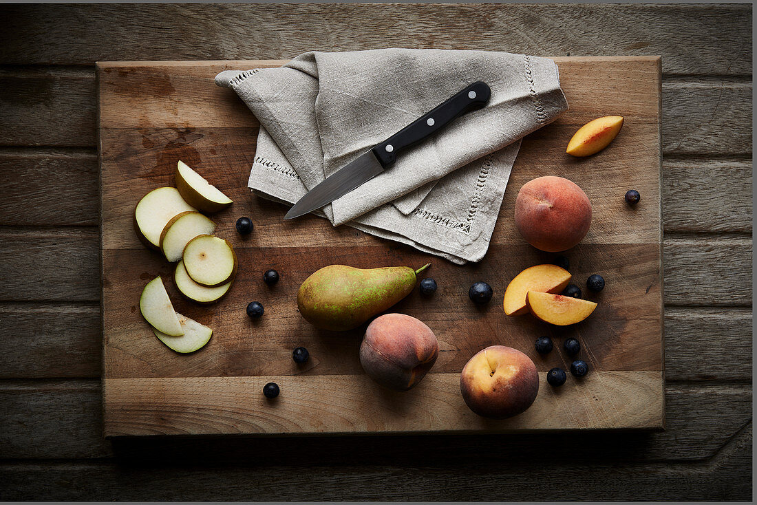 Pears sliced and whole with blueberries and peaches on a wooden chopping board