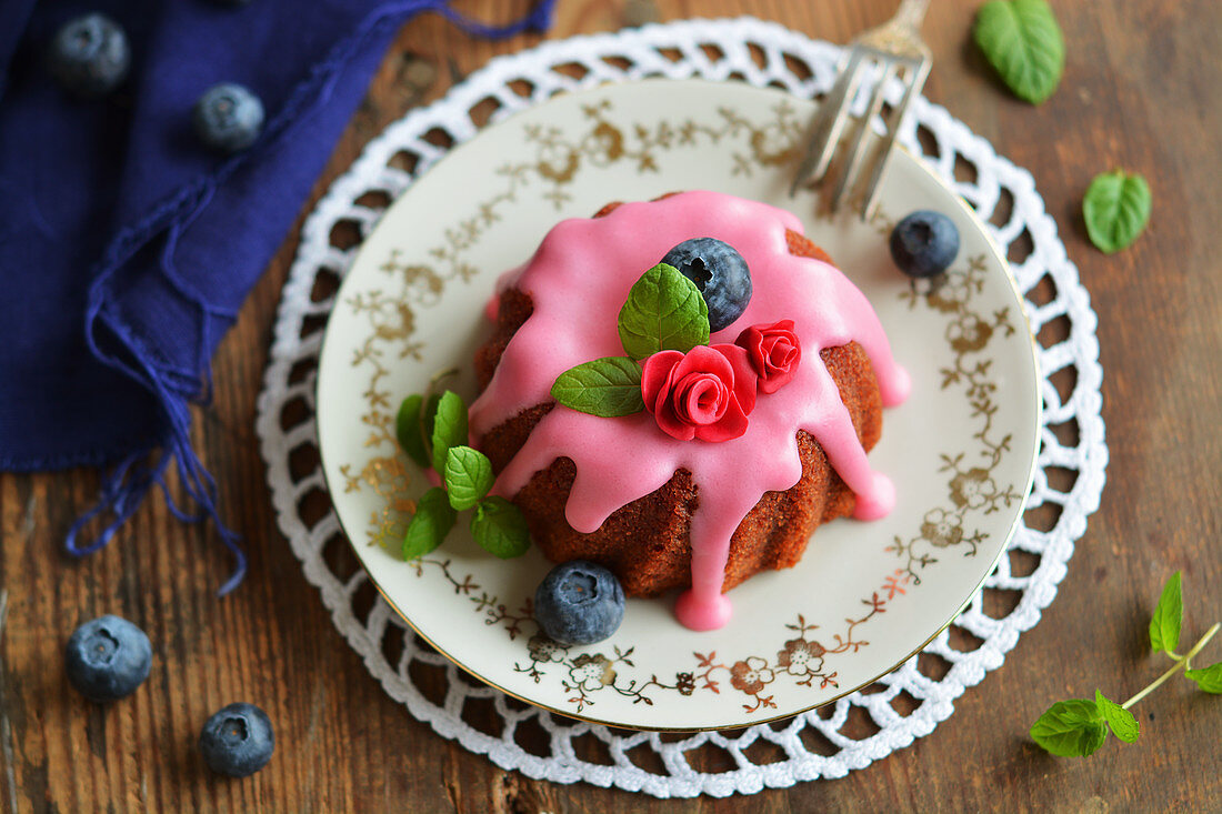 A mini gugelhupf with beetroot, frosting, sugar flowers, fresh blueberries and mint