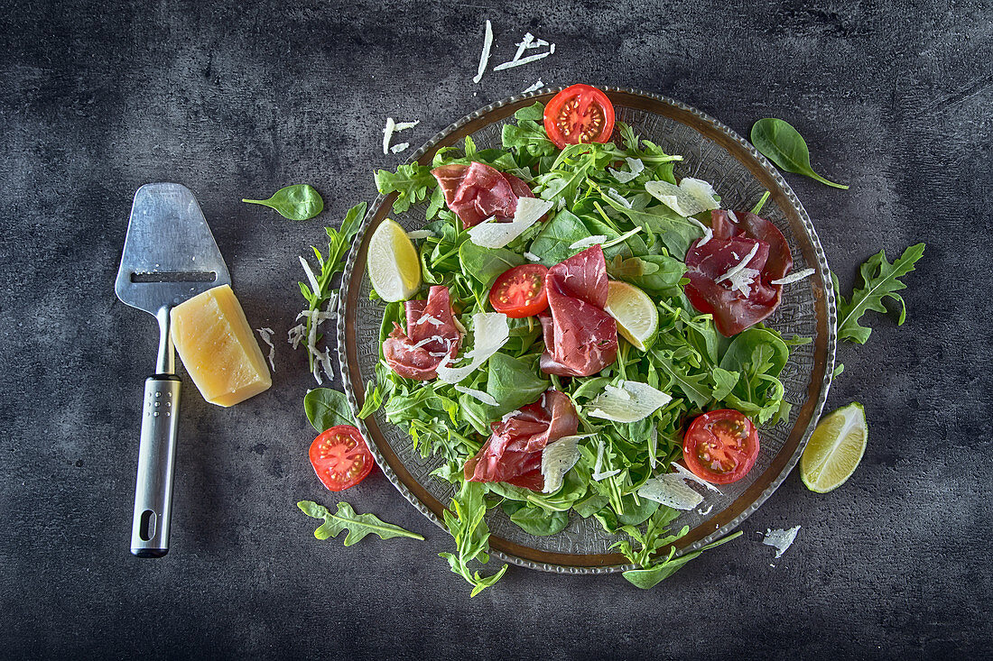 Salad bresaola with arugula, baby spinach, tomatoes, lime and cheese parmesan