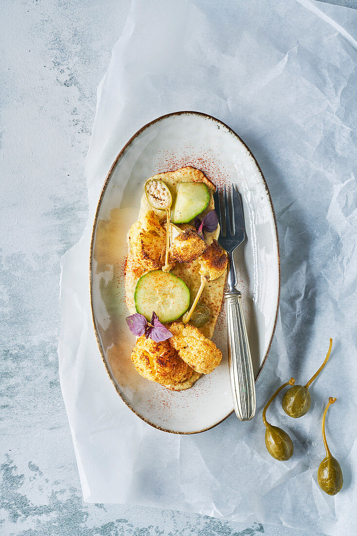 Roasted cauliflower with almond puree, apple capers, pickled cucumber and spring onion