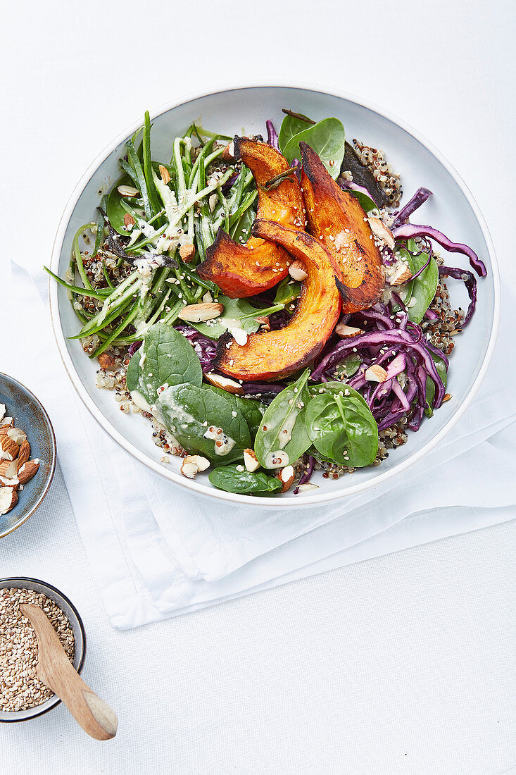 A quinoa bowl with pumpkin, spinach and red cabbage