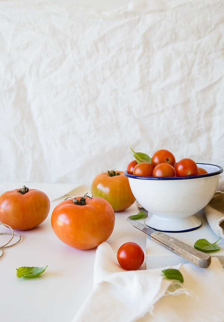 Various tomatoes in and beside a bowl
