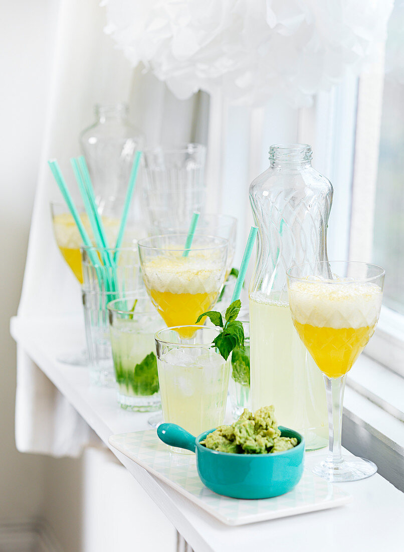 Lemonade in bottles and glasses with guacamole for a summer party