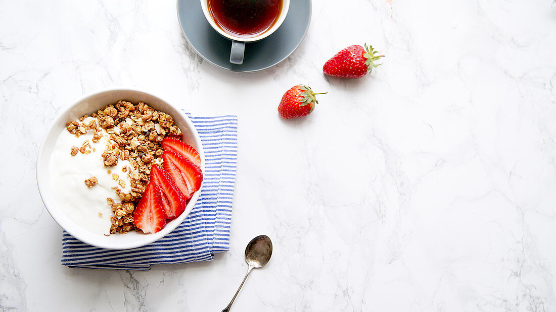 Crunchy granola with yoghurt and strawberries with a cup of black coffee on marble table
