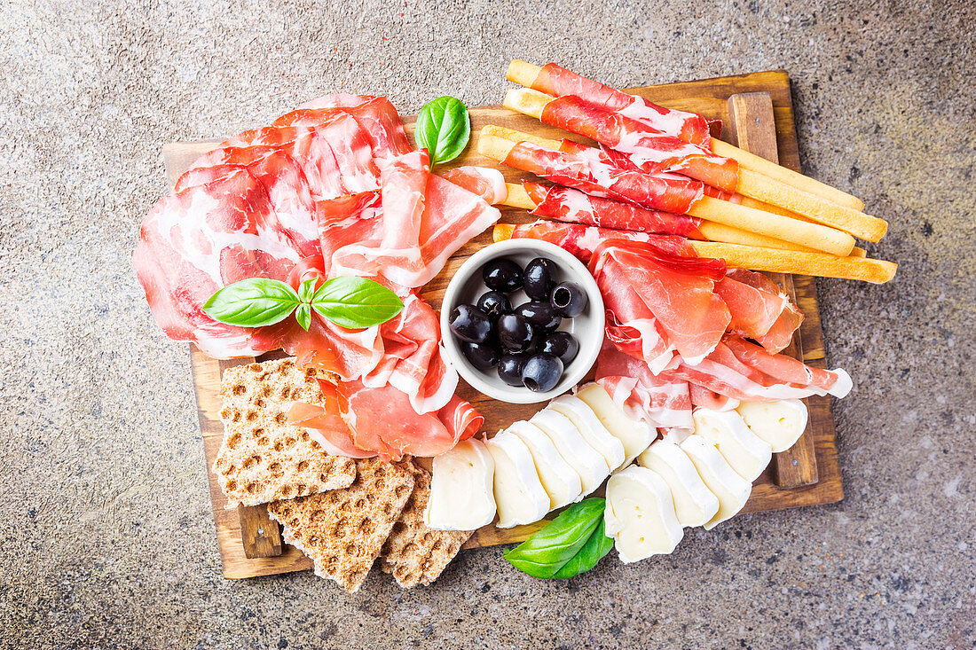 Cold meat plate with cheese, olives and bread on cutting board over gray stone background