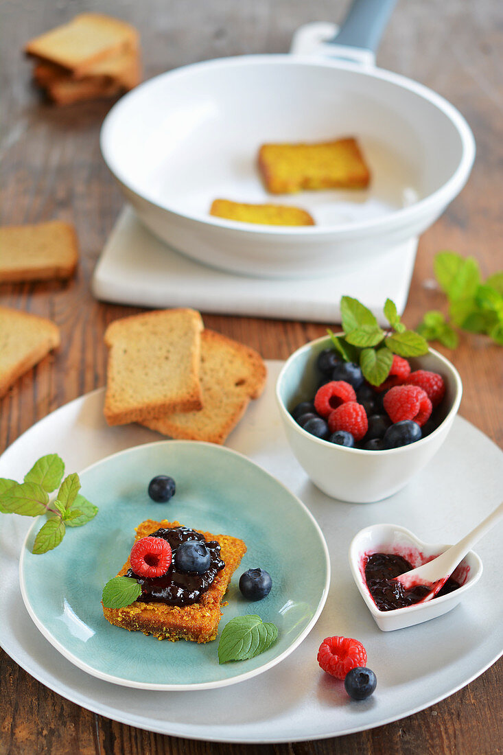 Rusk poor knight with jam and fresh fruits on a tray (vegan)
